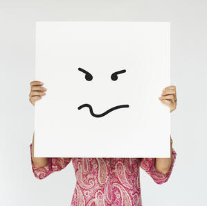 woman-holding-angry-banner-cover-her-face